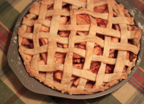 Top-down view of an apple pie with a lattice-work crust. It's sitting on a plaid tablecloth.
