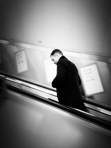 Man on an escalator by Fitzrovia