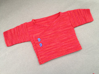 Lovely baby sweater knit of sock yarn with blue buttons