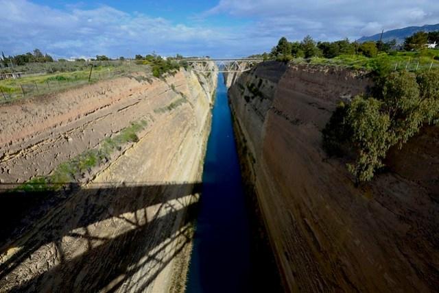 科林斯運河 (Corinth Canal) 將伯羅奔尼撒半島與希臘大陸分割開來,是十九世紀末期由法國人出資完工,本身具有八十餘公尺的深度,兩岸岩壁鑿痕明顯,幾近垂直的陡峭,站在橋面上可以吹著呼呼海風,甚至可以進行高空彈跳的活動。其全長為 6.3 公里,北望可見科林斯灣 (Gulf of Corinth),南向則為薩龍灣 (Saronic Gulf),伯羅奔尼撒半島就這麼變成了個真正的大島,實在令人震撼。