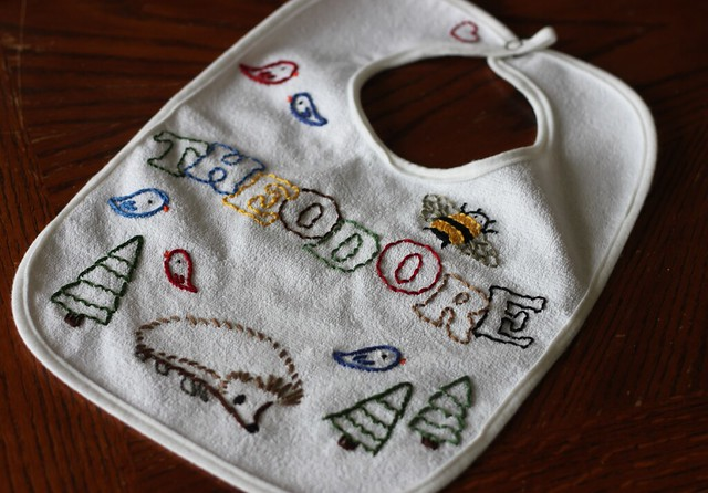 Hand-embroidered baby bib. It has images of little birds, a bumblebee, a hedgehog, and trees, along with the name