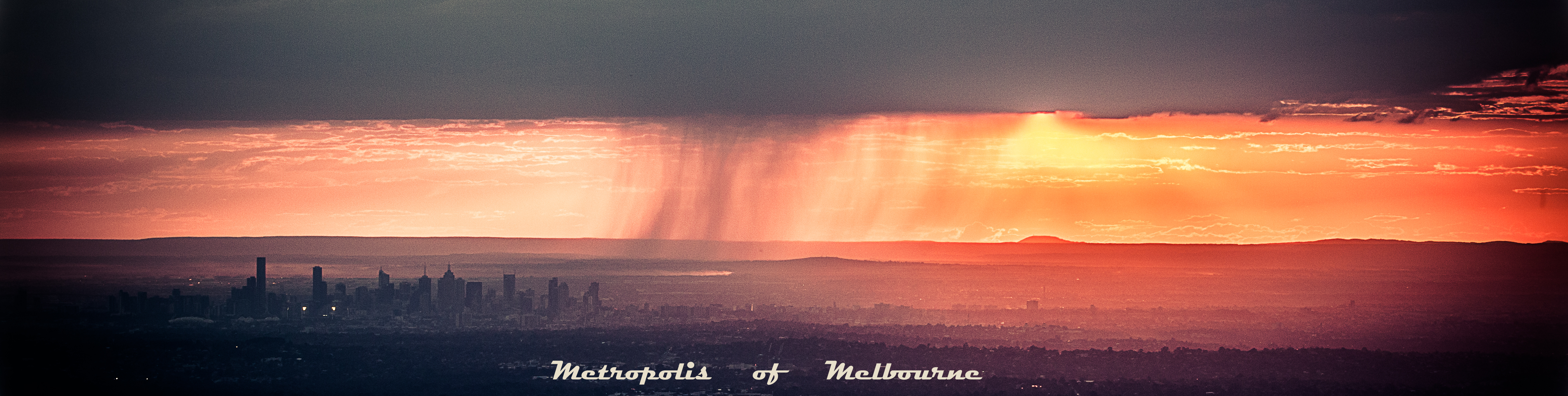 A sunset over Melbourne Australia with a rain cloud