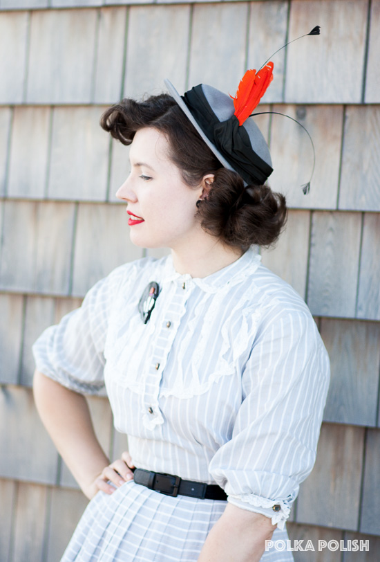 A badger brooch and a silly hat with orange and black feathers add a pop of color to a monochrome 1950s inspired daywear outfit