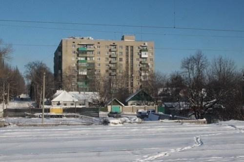 Soviet-era apartment blocks tower over older cottages