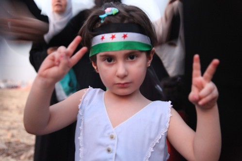 Small child shows peace signs standing at the feet of her mother in an anti-regime demonstration outside the Syrian Embassy in Jordan by JessicaOmari