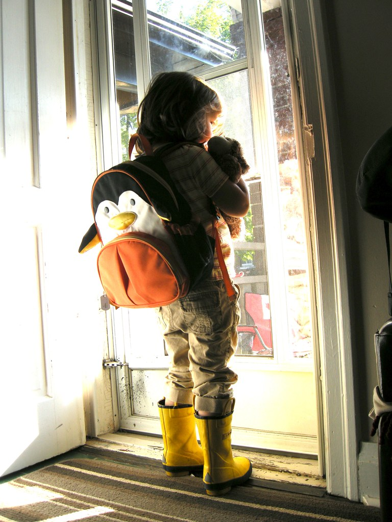 photo of a child with a backpack ready to head out the door to school