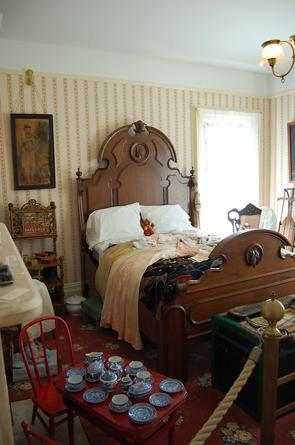 ornate maple bed with at small children's table in front set with toy china.