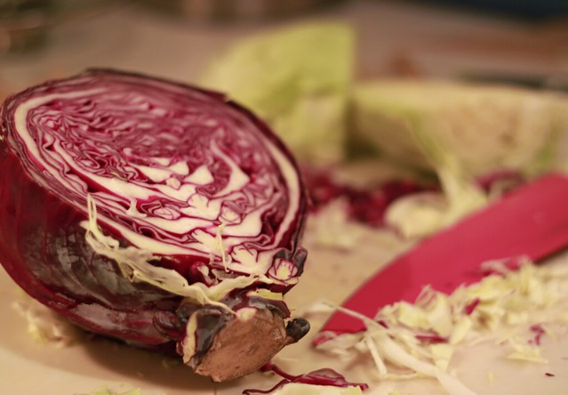 Wide shot of a clear plastic cutting board. In the foreground is half a purple cabbage. In the background is a pink chef's knife and lots of green cabbage, some in wedges and some sliced thinly.