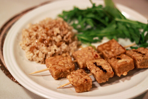 White plate with two tempeh kebobs, an arugula side salad, and a small mound of brown rice drizzled with sauce.
