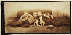 Čtyři pololežící děti – tři chlapci s jednou dívenkou; před nimi položeny dva kloboučky