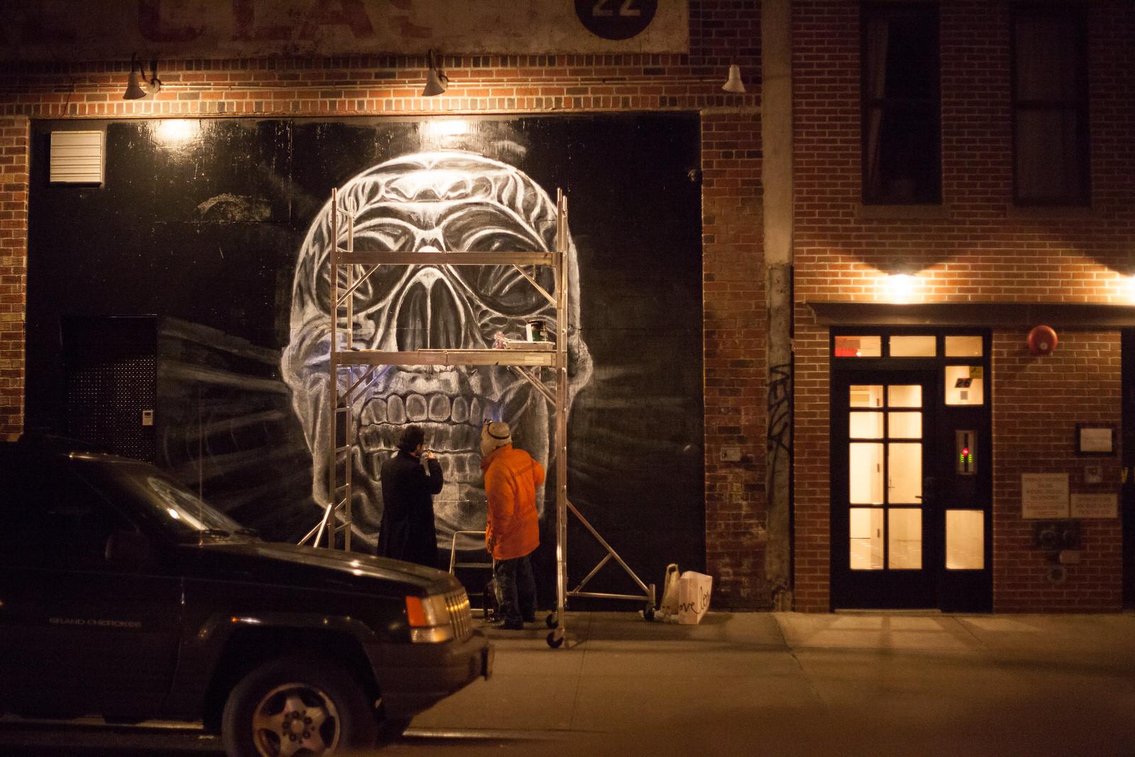 Artist drawing an enormous skull in chalk by wwward0