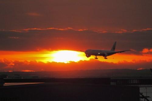 初日の出を横切る飛行機