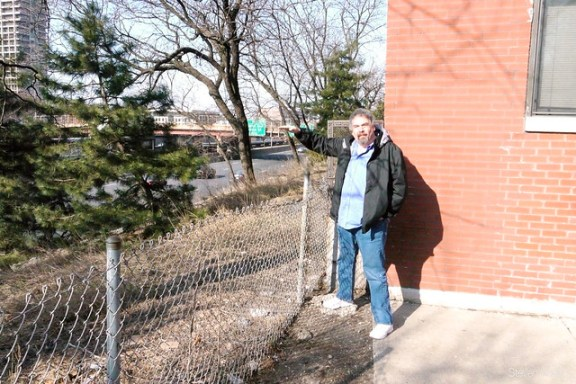 Condo board president David Lewis shows the approximate height of the top of the retaining wall that would be 7.5 feet away from the building