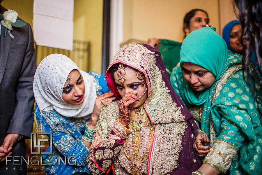 Bride wiping a tear from her eye during Indian wedding Nikkah ceremony