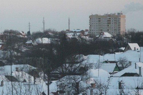 Soviet-era apartment block towers over snow covered houses in Таганрог (Taganrog)
