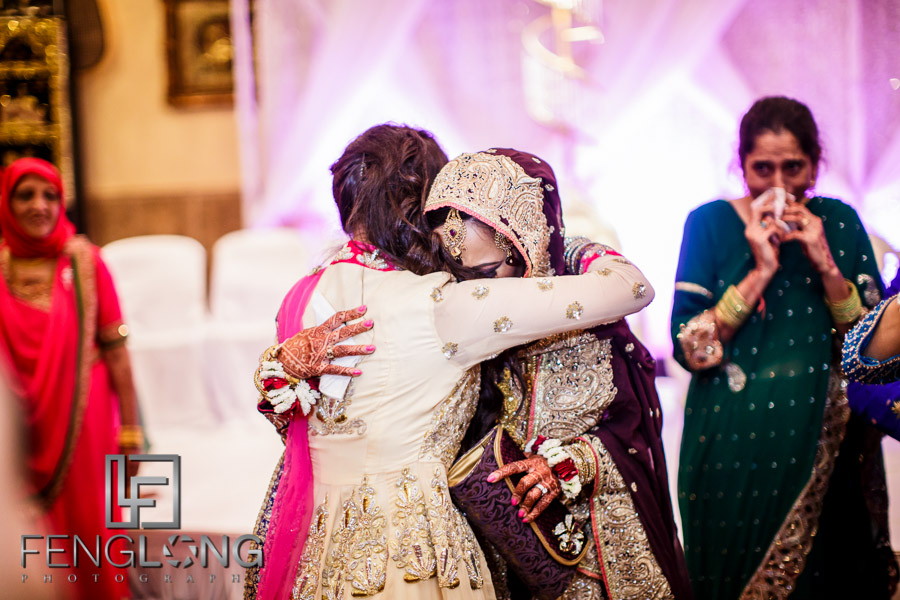 Indian bride hugging her sister and crying during her Rukshat exit ceremony