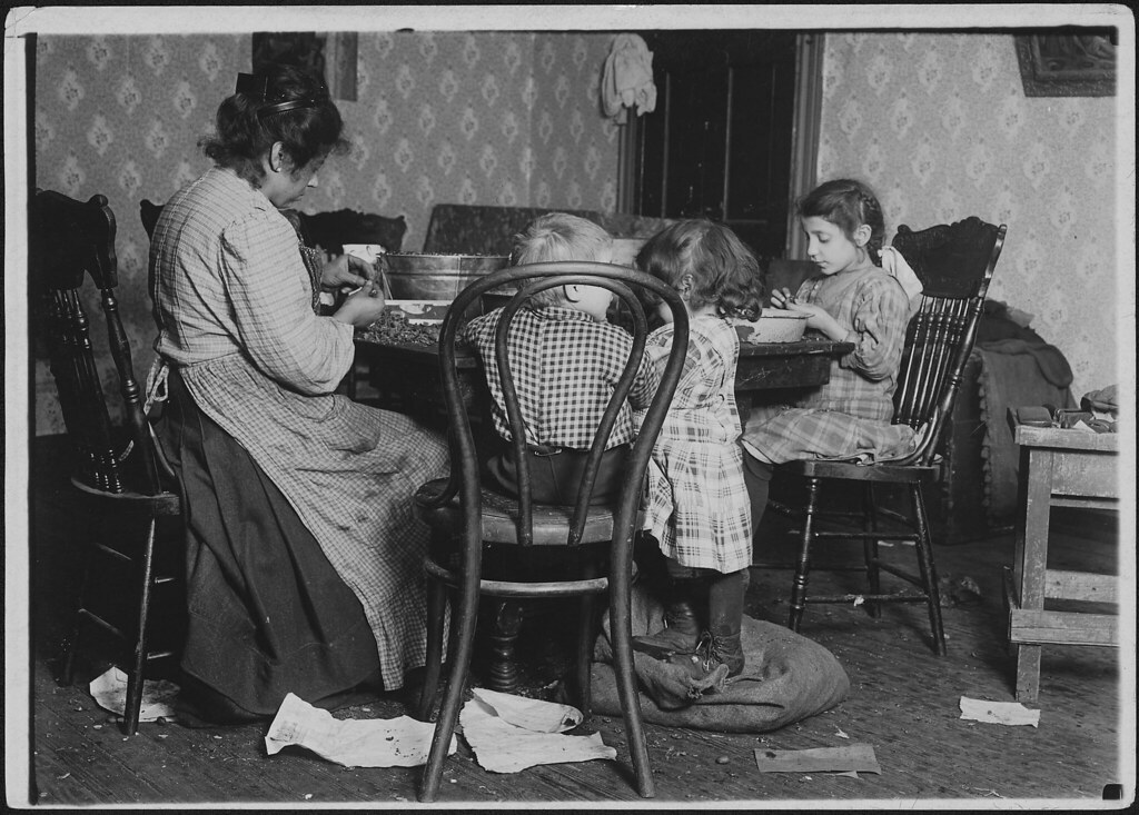 Mrs. Lucy Libertime and family, Johnnie, 4 years old, Mary 6 years, Millie, 9, picking nuts in the basement tenement, December 1911