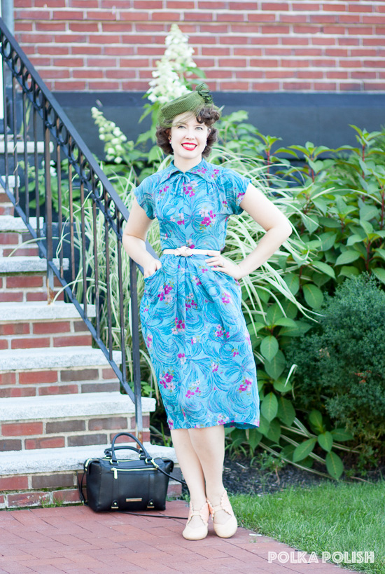 1940s bow and flower print dress in bold aqua paired with an olive tilt hat and shell pink shoes