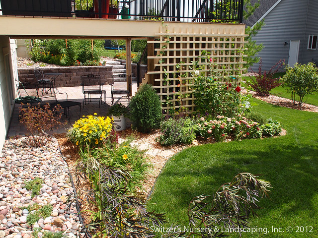 The custom made trellis and the planting bed further create the feeling of an outdoor garden room under the deck.