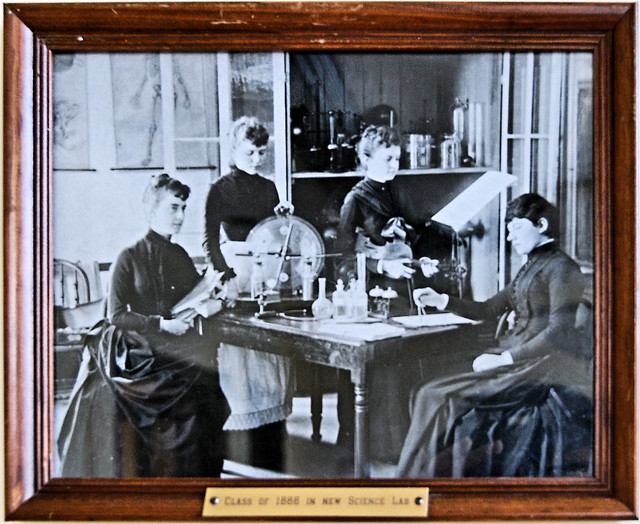 Women in period dress at a table with various chemistry glass ware behind them in the other room you can see full size diagrams of human anatomy