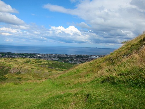 Spectacular view of Edinburgh - green hills in the foreground, the city in the mid-ground, and the water in the background.