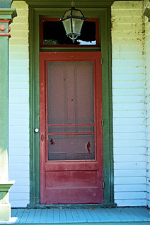 Servants entrance with will worn torn screen door and dirty clapboard, still painted red