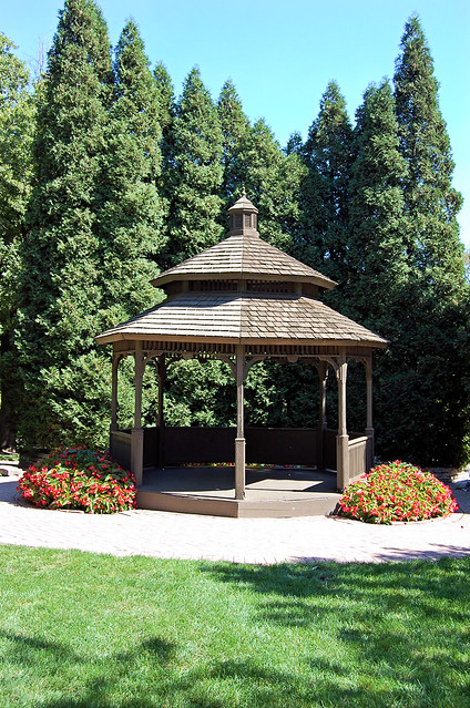 An octagonal brown gazebo with tall tree windbreak behind it.