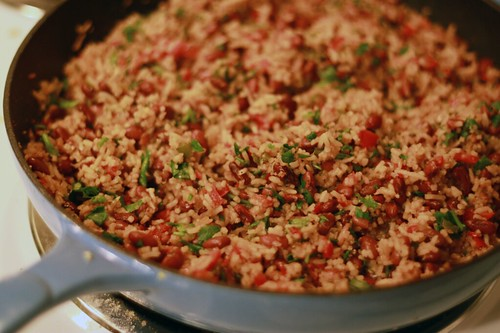 Close-up of a cast-iron pan with a rice and beans mixture cooking. It has lots of visible diced veggies and spices.