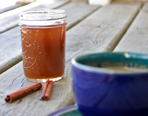 Unfocused small blue teacup in the foreground with an in-focus jar of an orange-brown syrup in the background. Next to the jar are two cinnamon sticks.