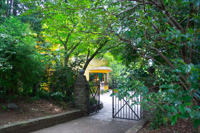 Entrada lateral al museo Ghibli, escondida entre árboles