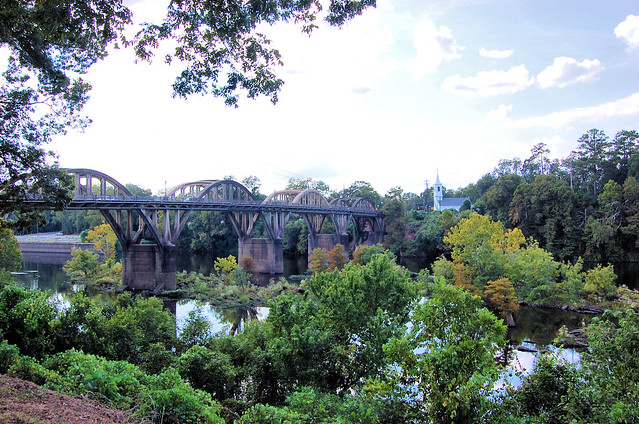 shot of arched bridge over Coosa River in Wetumpka.  The trees are changing color and a white church is in the background.