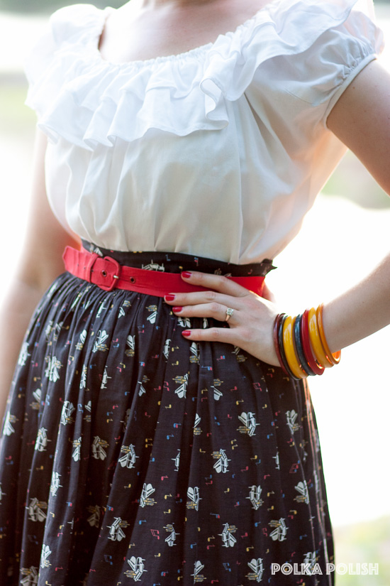 A dramatically ruffled peasant blouse paired with a vintage 1950s piano and music note novelty print skirt is set off by a red belt and a stack of primary colored Bakelite bangles