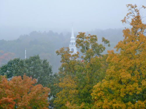 Church spire and fall foliage viewed from rainy window