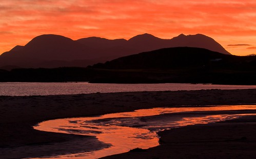 A picture of mountains in the distance against a red sunset sky with sea in the middle and a flow of water through a beach in the foreground