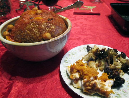 In the foreground is a small plate with roasted cauliflower and sweet potato casserole. In the background is a bowl filled with a bread bowl filled with stew!