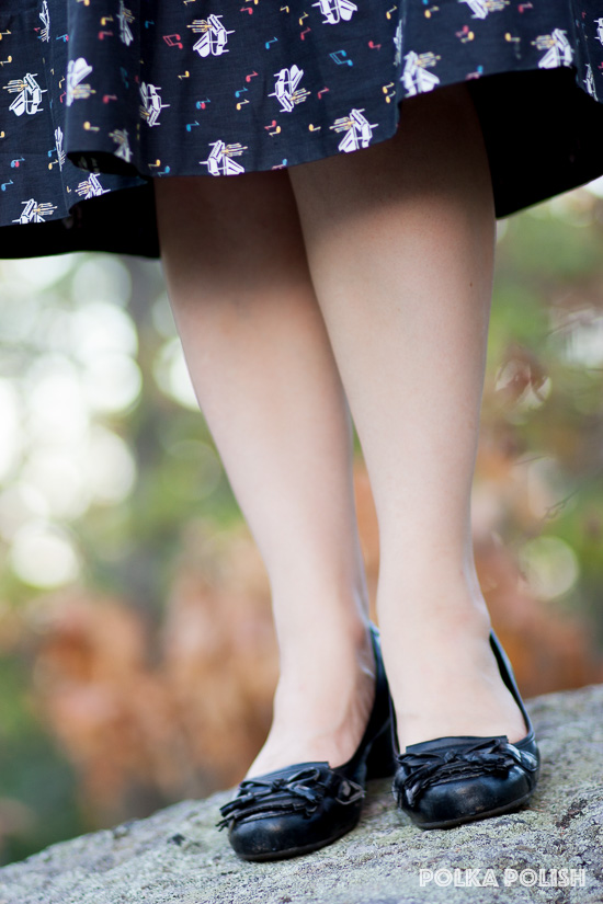 Black low-heeled loafer pumps with a 1950s vintage music novelty print skirt