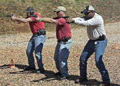 3 men shooting handguns at a range