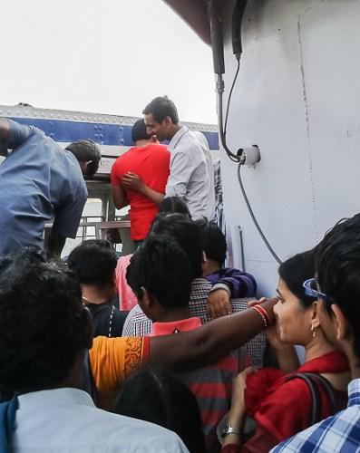 guys jumping and pushing to get in boat in Nagarjuna sagar