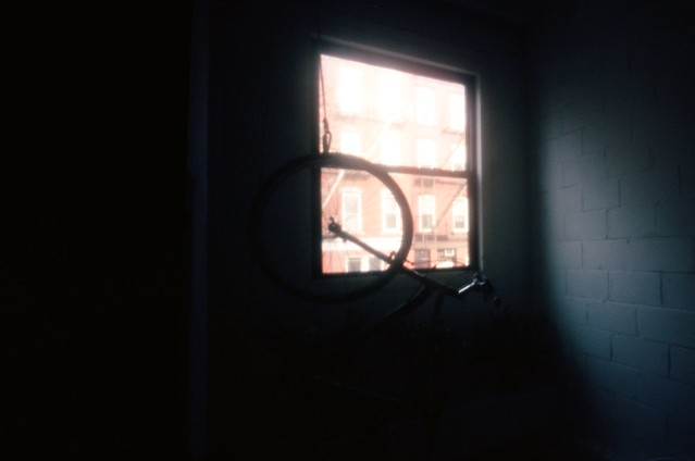 Someone's bicycle hanging on the wall; the staircase before her studio's entrance.