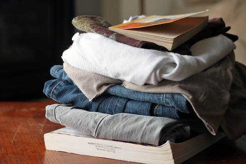 Small pile of folded jeans, shirts, and a couple of books.