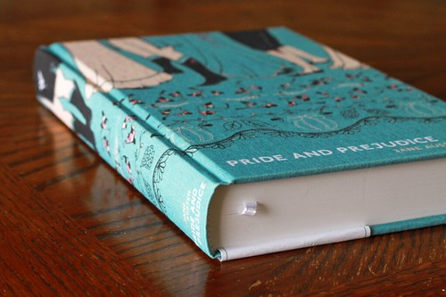 Book with a turquoise cloth cover, which features the feet and legs of folks dancing in old-fashioned clothes.