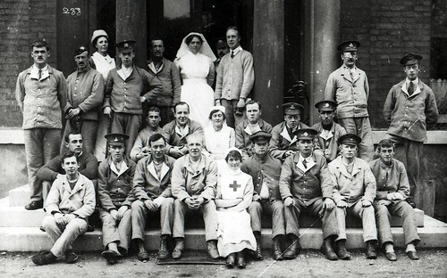 Nurses and soldiers on the steps of a hospital