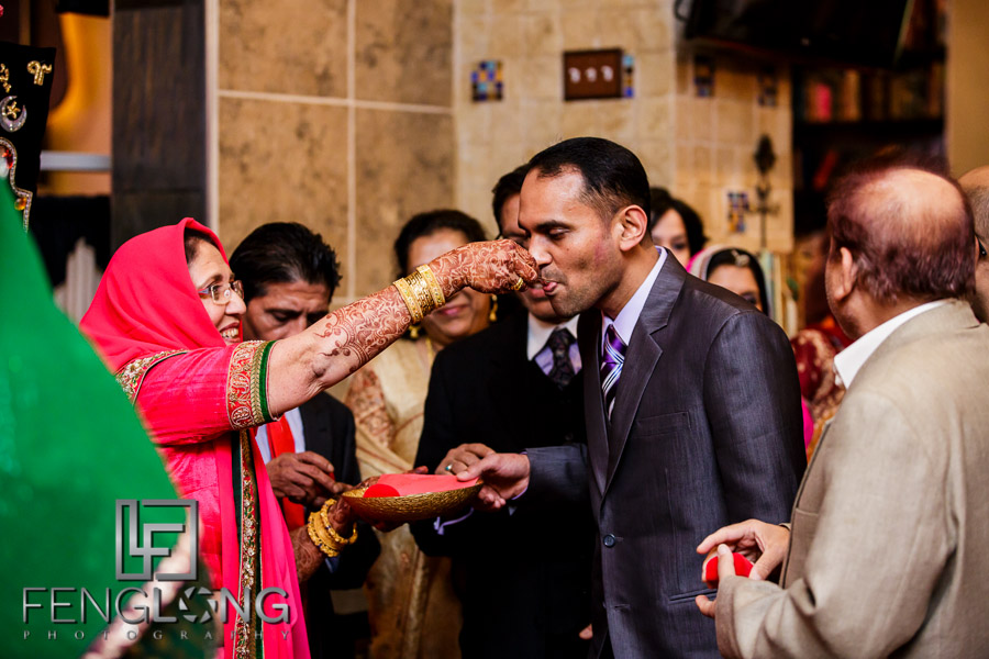 Indian woman feeding man on wedding day