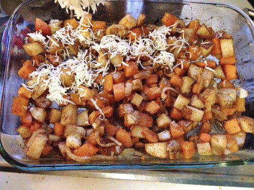 sprinkling cheese on roasted potatoes and butternut squash
