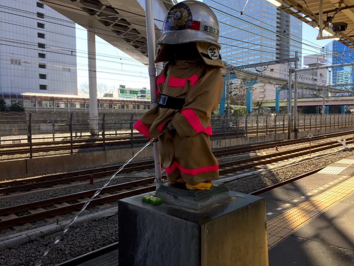 Peeing Boy Statue dressed up as a fireman at JR Hamamatsucho Station
