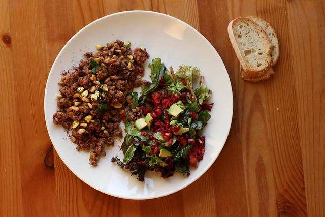 Ground lamb with pistachios, pine nuts, sumac, and a side salad on alickofsalt.com
