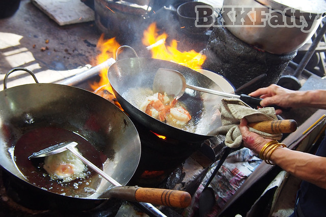 jay fai cooks jumbo shrimp over charcoal