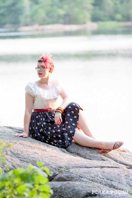 Sitting lakeside in a 1950s novelty piano print skirt with a white peasant blouse and red accents.