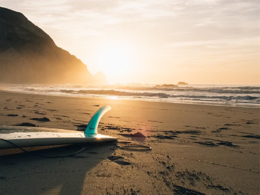 Foto gratis de de una tabla de surf en la arena de la playa