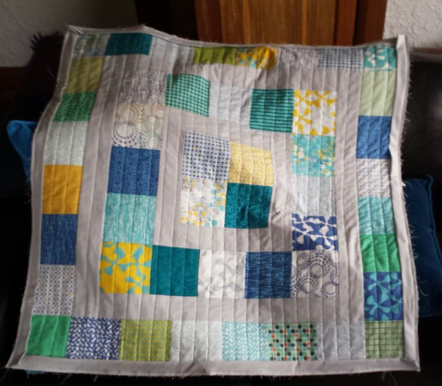 Baby quilt quilted and bindings sewn onto front. Now I just need more grey thread so I can hand sew them on the back.